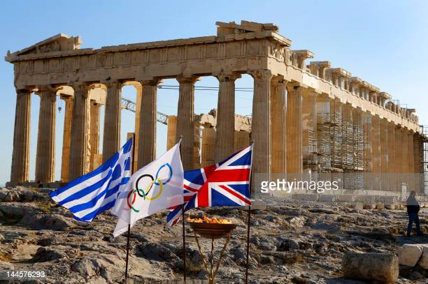 The cauldron with the Olympic Flame is seen past flags of Greece IOC and Great Britain atop the Acropolis in Athens on May 16 2012 The flame will be...