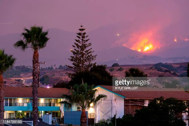 The Cave fire burns a hillside above houses in Santa Barbara California on November 26 2019 The winddriven brush fire that started late on November...