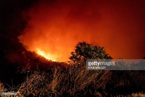 The Cave Fire burns a hillside near homes in Santa Barbara California early on November 26 2019 The winddriven brush fire that started late on...