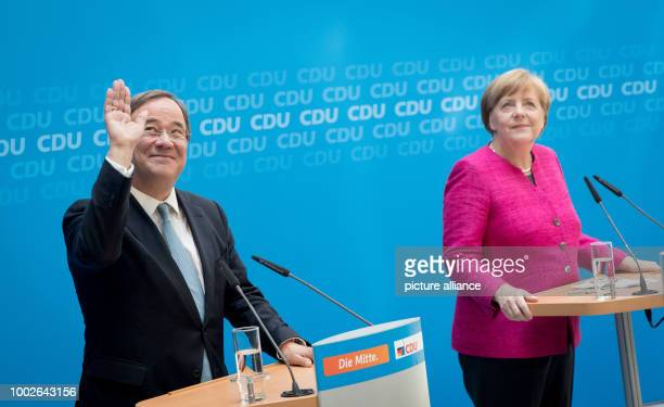 The CDU top candidate of the state elections in NorthRhine Westfalia Armin Laschet waves next to German chancellor and CDU federal chairwoman Angela...