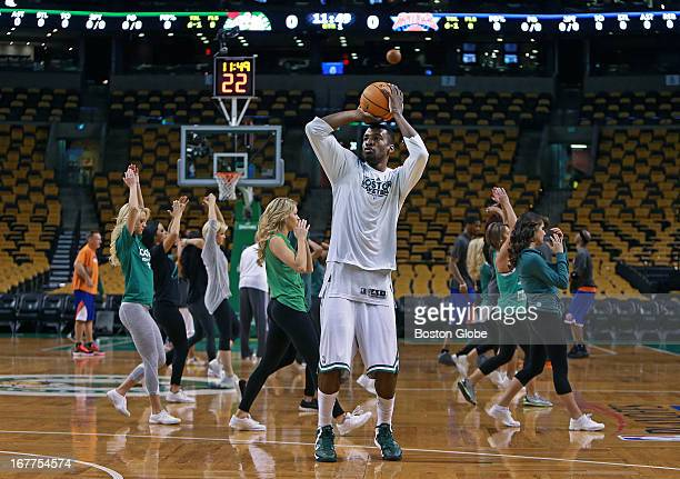 The Celtics Brandon Bass warms up in the foreground a couple of Knicks warm up in the background and the Celtics Dancers warm up in the middle The...