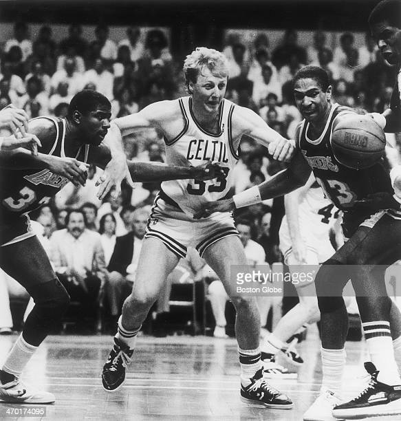 The Celtics' Larry Bird elbows his way between two Lakers players for a loose ball as the Boston Celtics play the Los Angeles Lakers at Boston Garden...