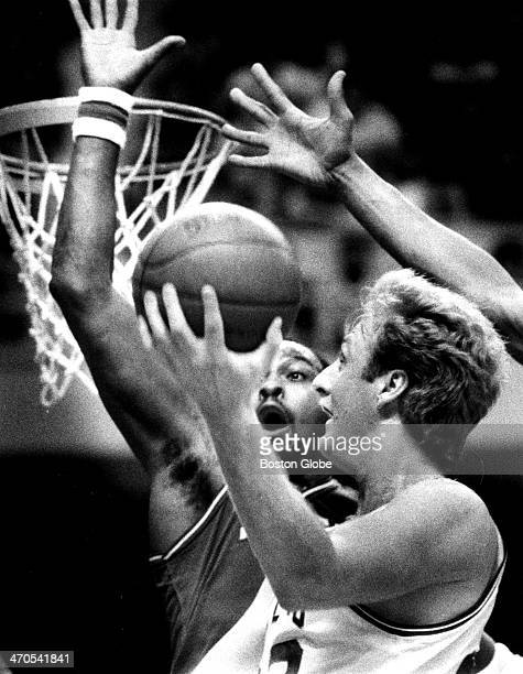 The Celtics' Larry Bird has his sight on the hoop as he shoots over the hands of a 76ers player at Boston Garden on May 12 1985