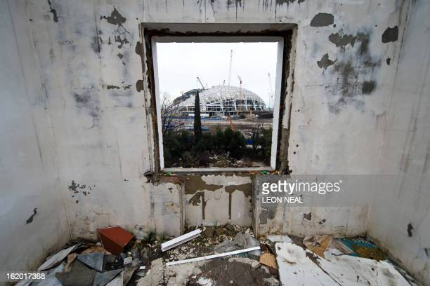 The Central Stadium for the Winter Olympics 2014 is seen through the window of a derelict house in Sochi on February 18 2013 With a year to go until...