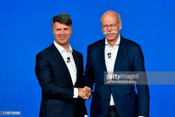 The CEO of German auto giant Daimler AG Dieter Zetsche shakes hands with CEO of German carmaker BMW Harald Krueger after they presented the merger of...
