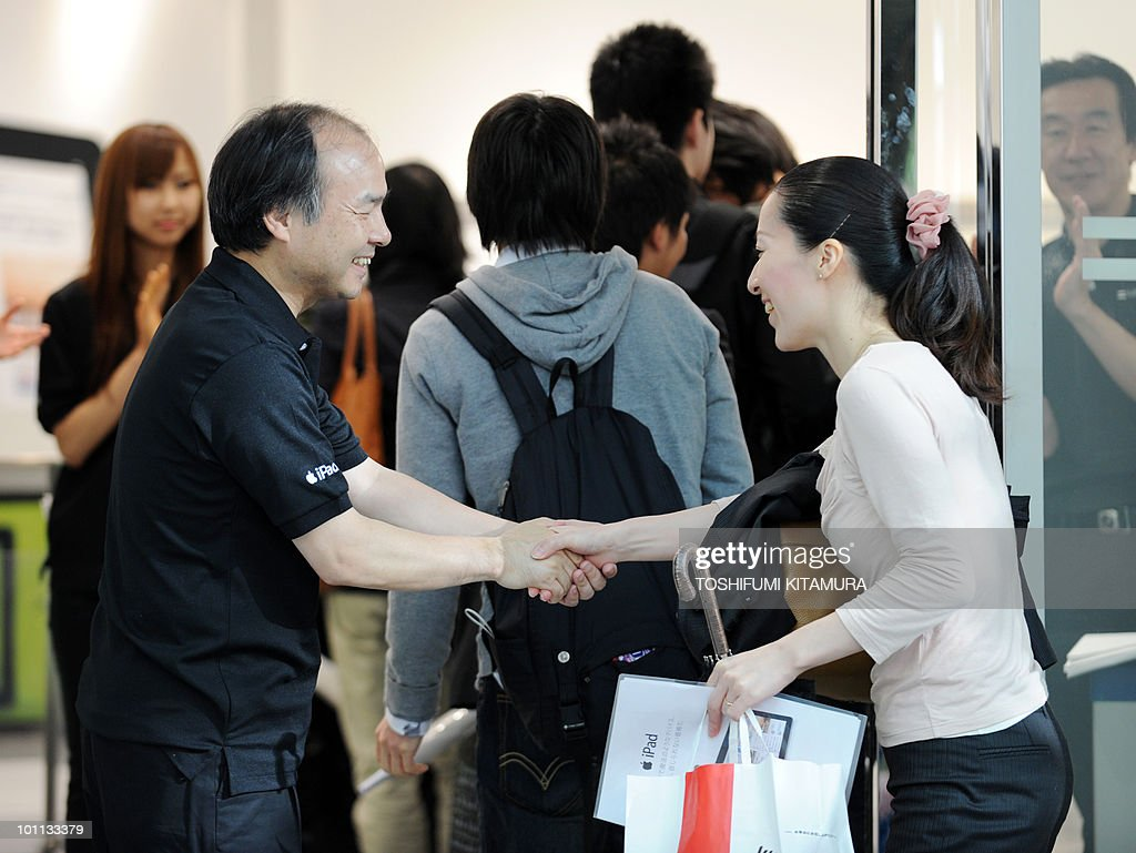 The CEO of Japanese internet service provider Softbank, Apple's exclusive partner in Japan, Masayoshi Son (L), shakes hands with customers in the shop in central Tokyo on May 28, 2010, as the iPad goes on sale. Apple's much-hyped iPad went on sale in a swathe of countries from Australia and Japan to Europe at the start of a global rollout tipped to change the face of computing.