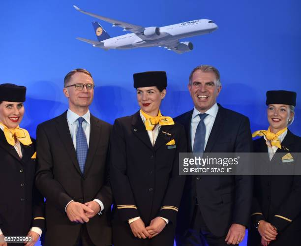 The CEO of the German airline Lufthansa AG Carsten Spohr and the CFO of Lufthansa Ulrik Svensson pose with stewardess after the annual press...