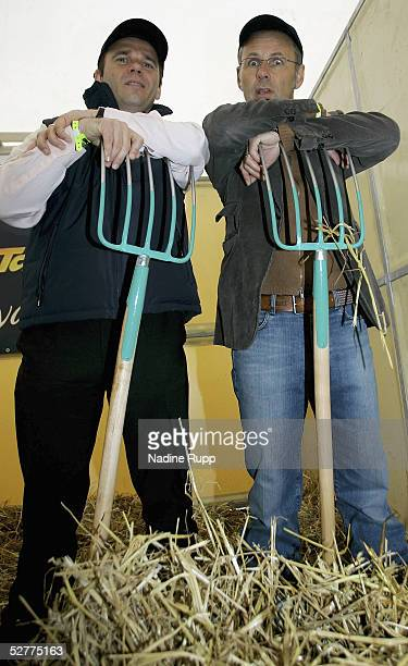 The CEO of the Hamburger SV Bernd Hoffmann and Reinhold Beckmann clean out a stable during German Jumping and Dressage Grand Prix at the Derby Park...