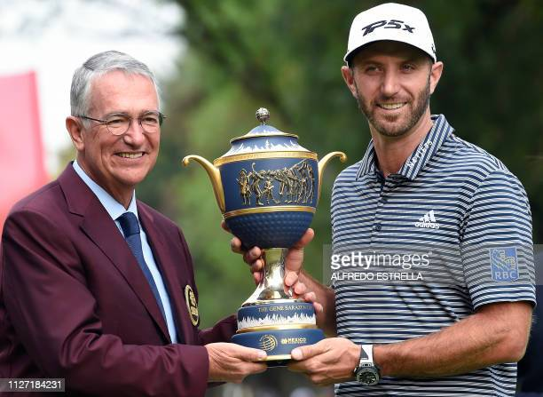 The CEO of the Salinas Group and organizer of the WGCMexico Ricardo Salinas poses with US golfer Dustin Johnson and the trophy after he won the World...
