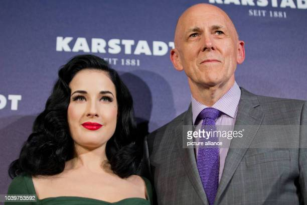 The CEO of the warehouse chain Karstadt Andrew Jennings and burlesque model Dita von Teese pose for the camera within a newly renovated Karstadt shop...