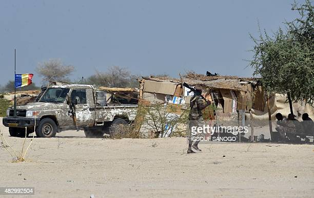 The Chadian flag flutters on the front of a military vehicle as soldiers from the Niger and Chadian army soldiers sit in the shade on May 25 2015 in...