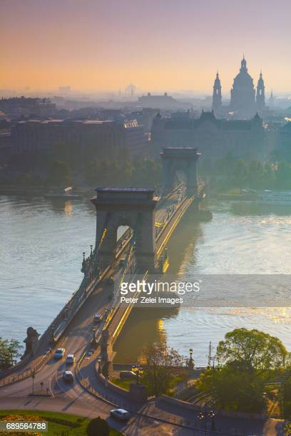 The Chain Bridge of Budapest at sunrise with the St. Stephen's Basilica in the background