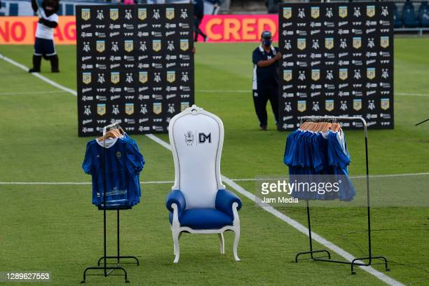 The chair of late Diego Maradona, former coach of Gimnasia y Esgrima La Plata, is displayed in the middle of the field while commemoratinve jersey...