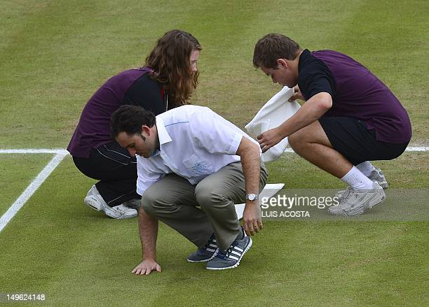The Chair Umpire checks the grass moments before Belgium's Steve Darcis and Spanish Nicolas Almagro play a men's single tennis Third round match at...