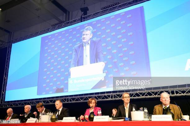 The chairman of the Alternative for Germany farright party Joerg Meuthen is seen on a giant screen while speaking as party's leadership members...