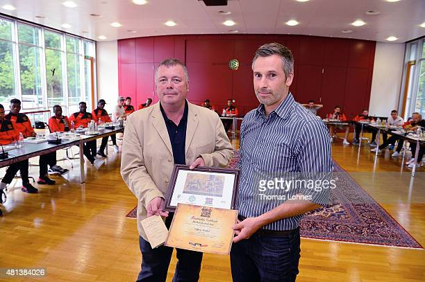 The chairman of the English football team Sheffield FC Richard Tims gives Peter Scheffler a copy of the 'Rules Regulation and Law' a membership...