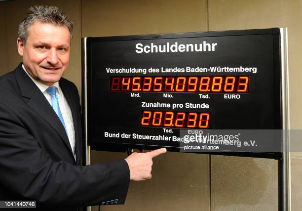 The chairman of the FDP's parliamentary fraction in the state parliament of BadenWuerttemberg HansUlrich Ruelke points at a national debt clock in...