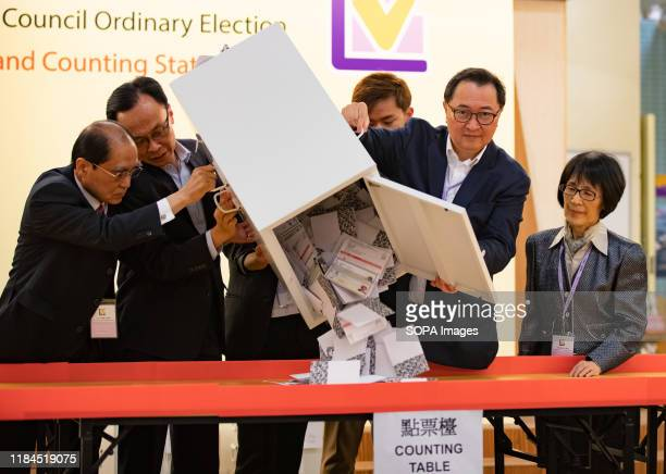 The Chairman of the HKSAR Electoral Affairs Commission Barnabas Fung pours down the ballots from a ballot box to be counted at a polling station...