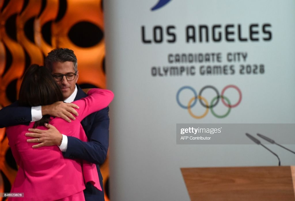 The Chairman of the Los Angeles 2028 bid, Casey Wasserman (R) and the Vice-Chair and Director of the Athlete Relations of the LA 2028 bid, Janet Evans, greet each other as they delivers their speeches during the 131st International Olympic Committee (IOC) Session in Lima on September 13, 2017. The ICO meeting in Lima will confirm Paris and Los Angeles as hosts for the 2024 and 2028 Olympics, crowning two cities at the same time in a historic first for the embattled sports body. / AFP PHOTO / Martin BERNETTI