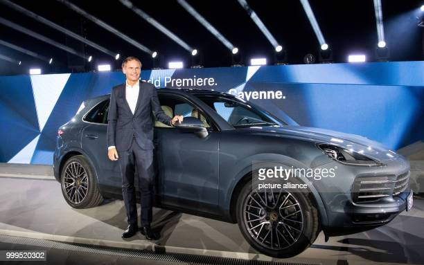 The chairman of the Prosche AG Oliver Blume stands next to a Prosche Cayenne vehicle during the introduction of the new Cayenne Generation at the...