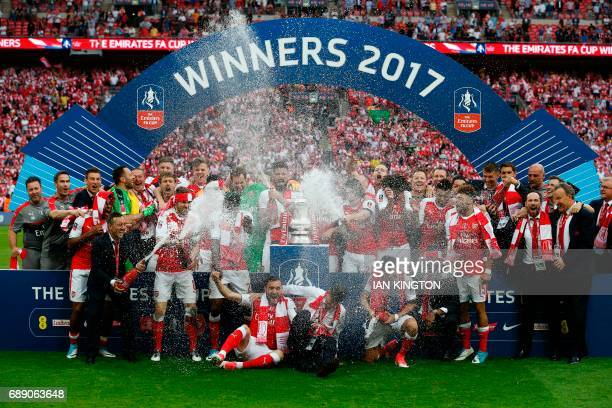 The champagne is sprayed as Arsenal's players celebrate after their win over Chelsea on the pitch after the English FA Cup final football match...