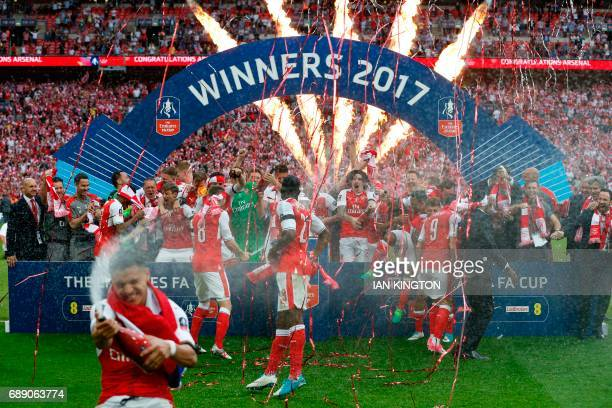 The champagne is sprayed by Arsenal's Chilean striker Alexis Sanchez as Arsenal's players celebrate after their win over Chelsea on the pitch after...
