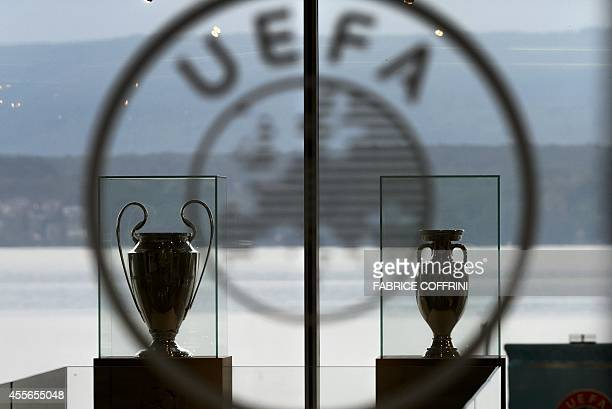 The Champions League and Europa League trophies are pictured at the entrance of the UEFA headquarters on September 18 2014 in Nyon AFP PHOTO /...