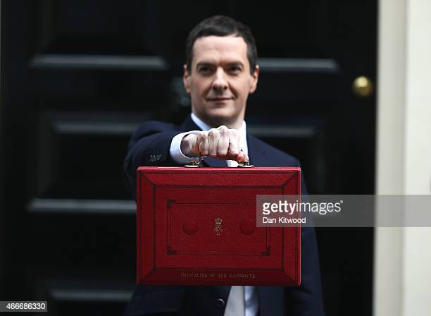 The Chancellor of the Exchequer George Osborne holds his ministerial red box up to the media as he leaves 11 Downing Street on March 18 2015 in...