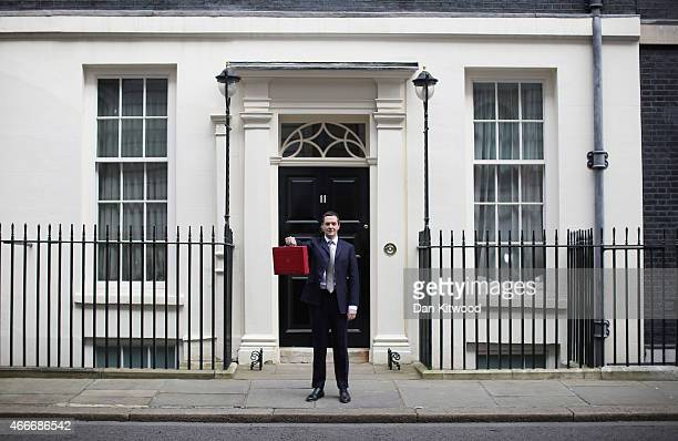 The Chancellor of the Exchequer George Osborne holds his ministerial red box up to the media as he leaves 11 Downing Street on March 18, 2015 in...