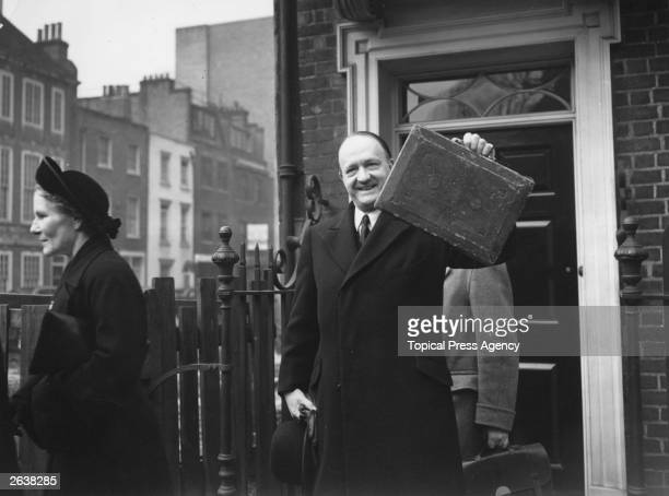 The Chancellor of the Exchequer Richard Austin Butler holds up the red bag outside his Smith Square home prior to the 1952 Budget the first...