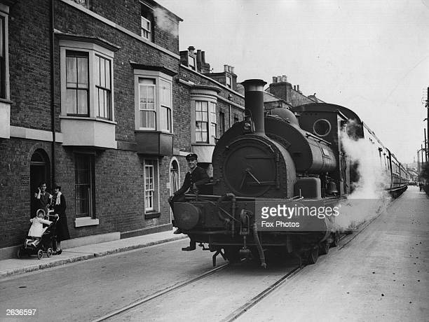 The Channel Islands Boat Express passes through the streets of Weymouth on its way to the quayside with the flagman on the front sounding a bell to...