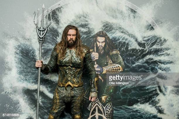 The character Aquaman from the Justice League film poses in character infront of film based promotional artwork unveiled for the first time during a...