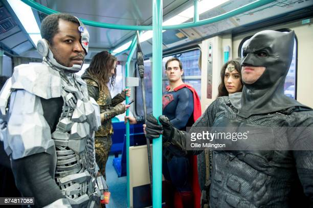 The characters Cyborg Aquaman Superman Wonder Woman and Batman from the Justice League film pose in character on the London Underground during a...