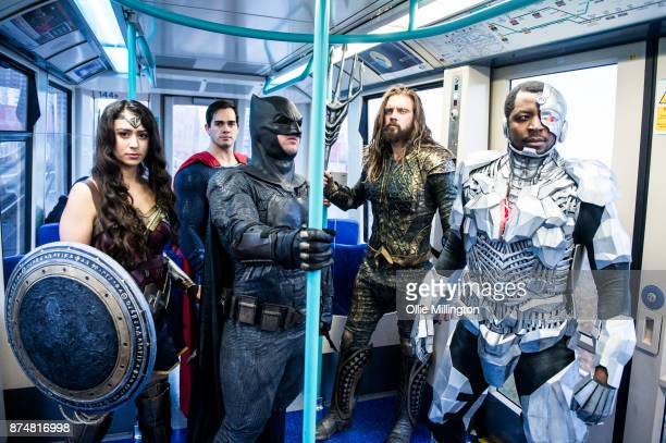 The characters Wonder Woman Superman Batman Aquaman and Cyborg from the Justice League film pose in character on the London Underground during a...