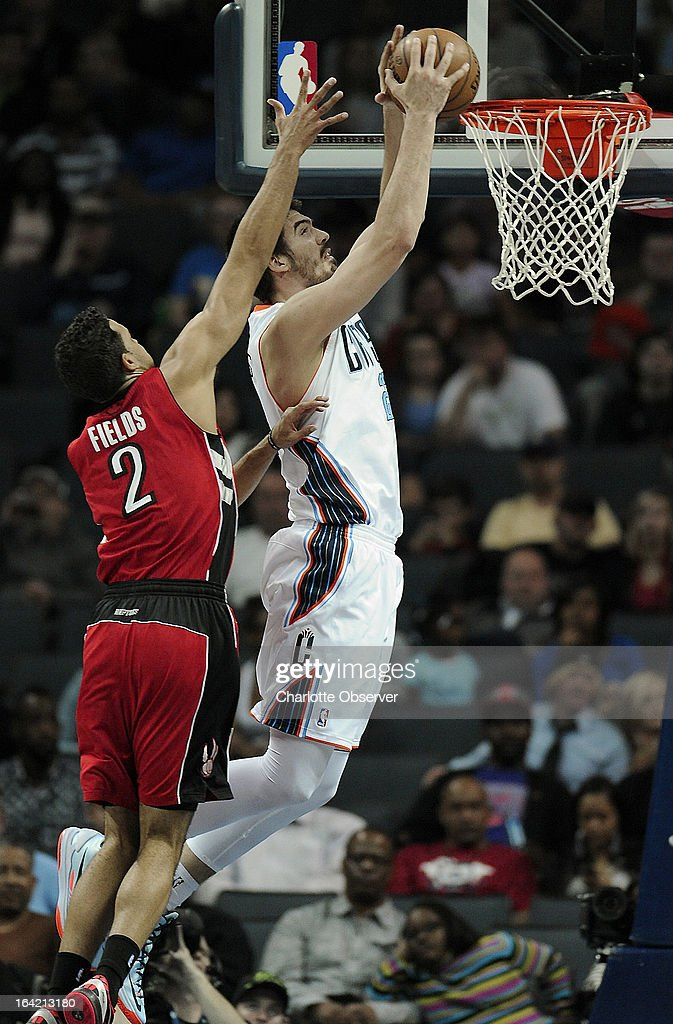 The Charlotte Bobcats' Byron Mullens drives to the basket for a two-handed dunk as the Toronto Raptors (2) Landry Fields applies defensive pressure during second-half action at Time Warner Cable Arena in Charlotte, North Carolina, on Wednesday, March 20, 2013. Charlotte won, 107-101.