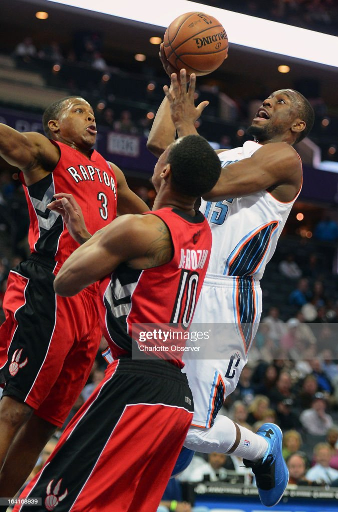 The Charlotte Bobcats' Kemba Walker drives to the basket as the Toronto Raptors' Kyle Lowry (3) and DeMar DeRozan (10) apply defensive pressure during first-half action at Time Warner Cable Arena in Charlotte, North Carolina, on Wednesday, March 20, 2013.