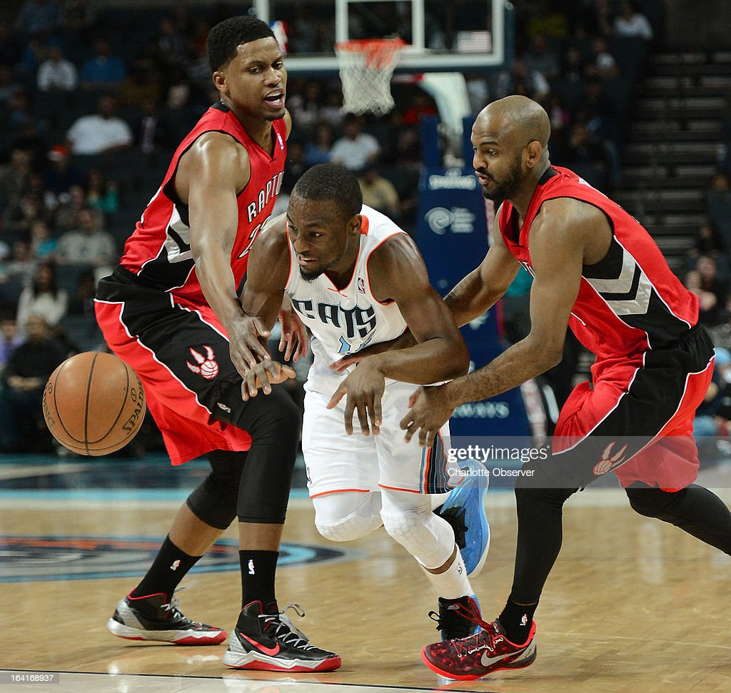 The Charlotte Bobcats' Kemba Walker fights to regain control of the basketball between the Toronto Raptors' Rudy Gay, left, and John Lucas III during first-half action at Time Warner Cable Arena in Charlotte, North Carolina, on Wednesday, March 20, 2013.