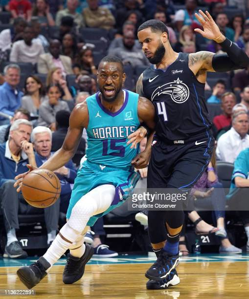 The Charlotte Hornets' Kemba Walker left fights his way to the baseline against the Orlando Magic's DJ Augustin right during the first half at...