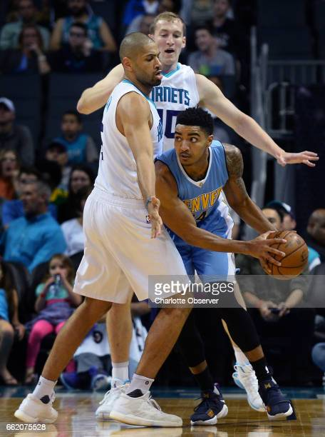 The Charlotte Hornets' Nicolas Batum left and Cody Zeller apply defensive pressure on the Denver Nuggets' Gary Harris in the first half on Friday...