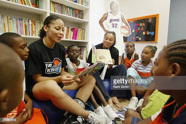 The Charlotte Sting players Dawn Staley and Allison Feaster read a book to the kids during the Grand Opening of Reading and Learning Center at the...