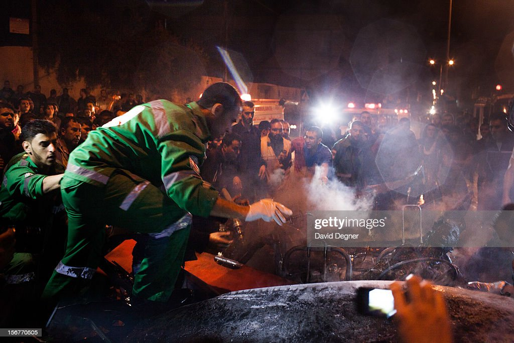 The charred bodies of two men are pulled out of their car on November 20, 2012 in Gaza City, Gaza. The health ministry identified them as Mahmud Koni and Hossam Salama, two cameramen journalists from Al-Aqsa TV channel.