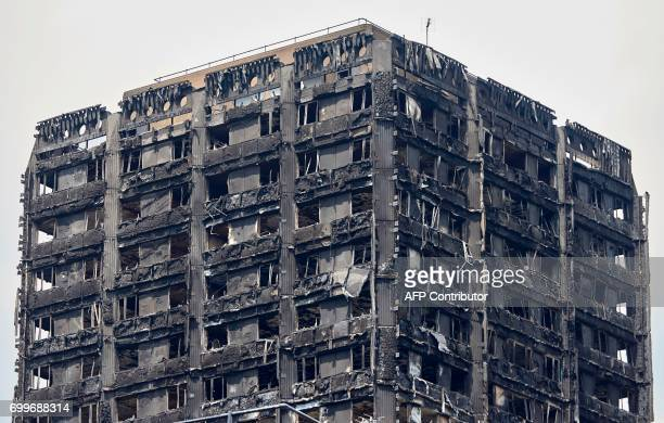 The charred remains of clading are pictured on the outer walls of the burnt out shell of the Grenfell Tower block in north Kensington west London on...