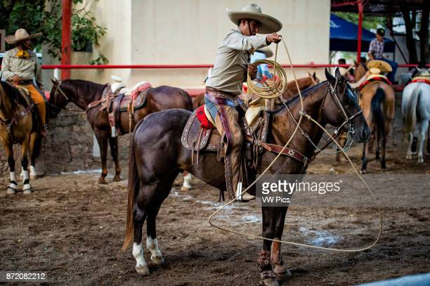 The charro twirls the rope in fancy patterns while he waitswithout watchingfor the mare