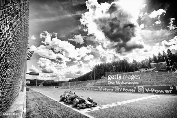 The checkered flag flies as Daniel Ricciardo of Australia and Infiniti Red Bull Racing crosses the finish line to win the Belgian Grand Prix at...
