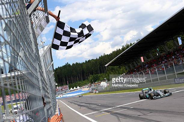 The checkered flag flies as Nico Rosberg of Germany and Mercedes GP crosses the finish line to claim victory in the Austrian Formula One Grand Prix...