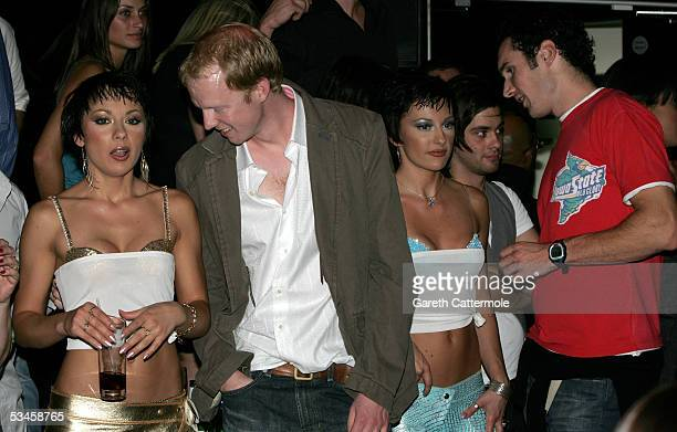The Cheeky Girls chat with unidentified men as they attend the Gridmodels 2006 Calendar Catwalk Competition at The Penthouse on August 24 2005 in...
