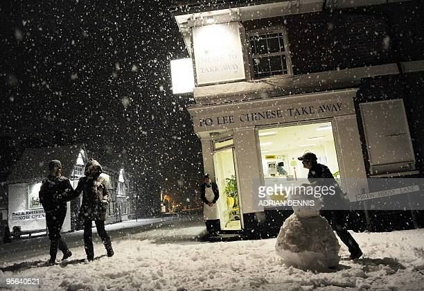 The chef from a Chinese Takeaway builds a snowman outside his restaurant in The High Street of Hartley Wintney 40 miles west of London on January 5...