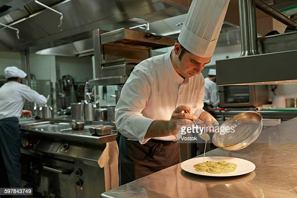 The chef serves in a restaurant kitchen