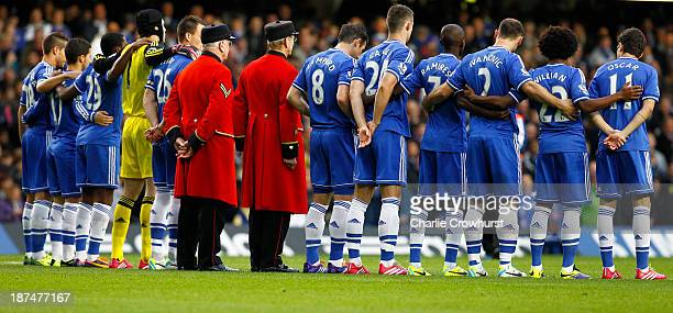 The Chelsea team stand with two Chelsea Pensioners as they mark a minutes silence during the Barclays Premier League match between Chelsea and West...