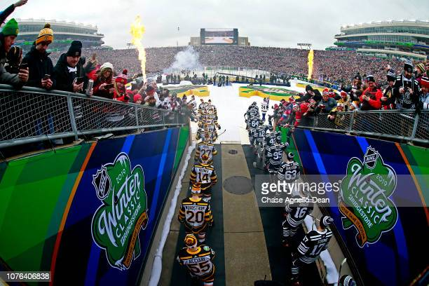 The Chicago Blackhawks and the Boston Bruins walk out to the ice during the 2019 Bridgestone NHL Winter Classic at Notre Dame Stadium on January 1...
